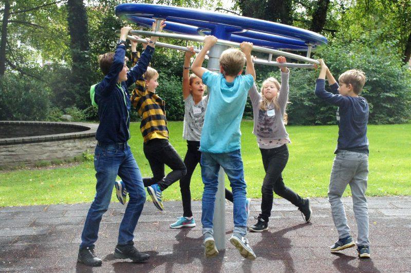 Kinder hängen an einem Spielgerät auf einem Spielplatz